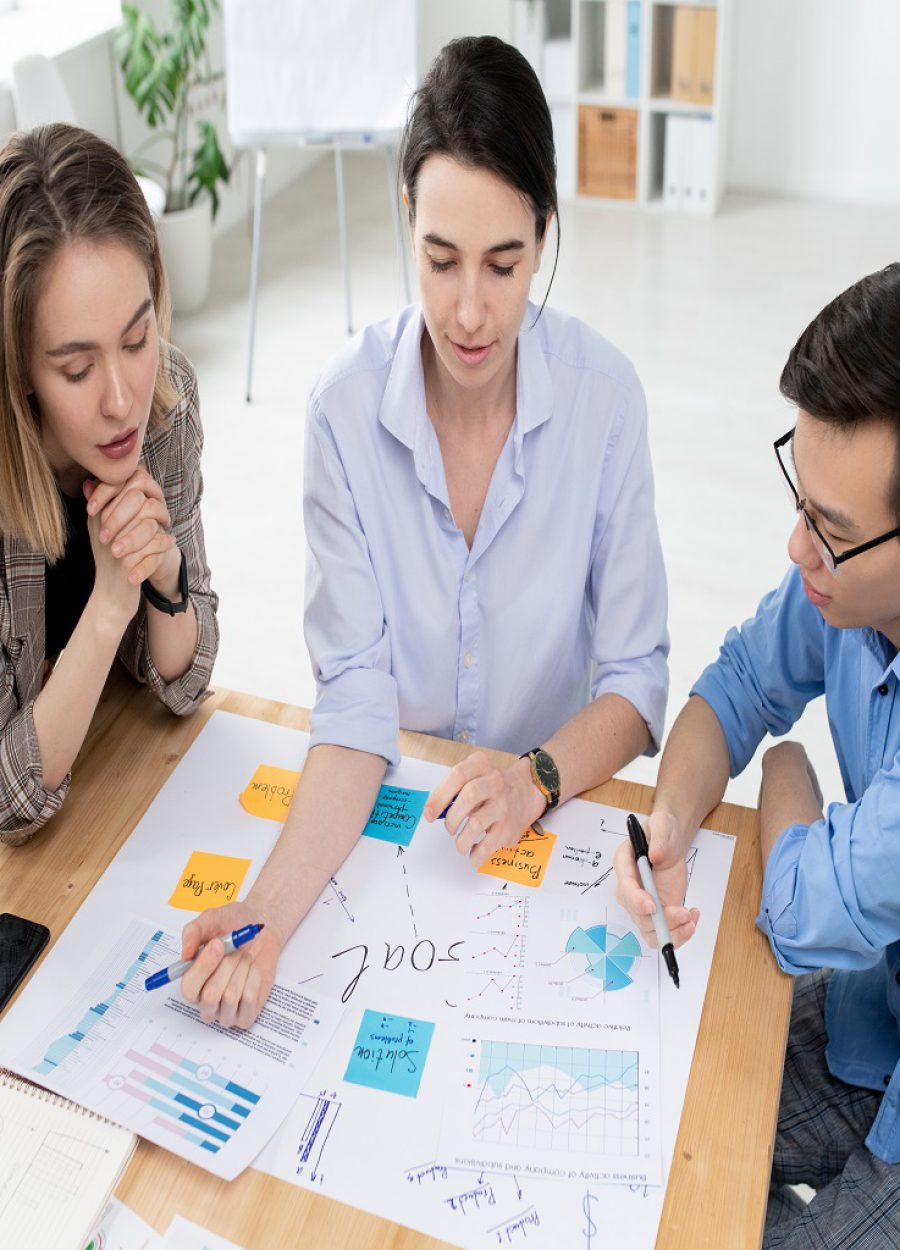 Two young women and businessman looking at large paper with business goals while brainstorming and discussing new ideas at meeting