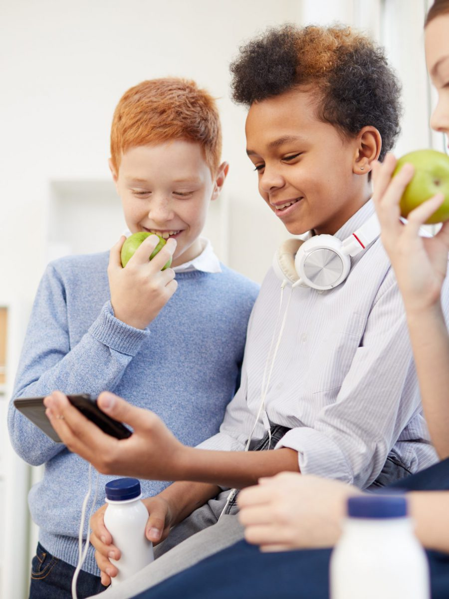 Group of school children eating milk and drinking fruit and using mobile phone during a break at the classroom at school